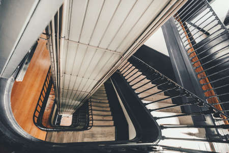 Photo pour Wide-angle view from above of a long stairwell going down in a spiral in an old dwelling house with a metal railing and a lift shaft in the center, selective focus in the foreground, Lisbon, Portugal - image libre de droit