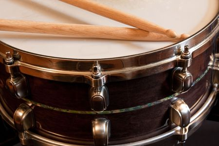 A snare drum with drumsticks resting on the skin