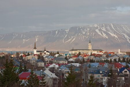 A view of Reykjavik, capital of Iceland, showing buildings, plants & the mountains behind the city