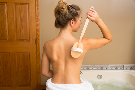 Photo pour Young woman sitting on edge of bath holding wooden-handle dry brush to her bare back - image libre de droit