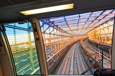 Speedy train on railway in iron frame tunnel above ocean in beautiful sunset ambient