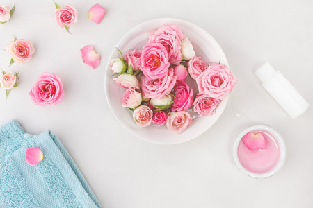 Photo pour Spa settings with roses. Fresh roses and rose petals in a bowl of water and various items used in spa treatments - image libre de droit