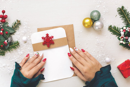 Photo for Christmas Card. Woman hands holding  a letter over festive table with various  items and gift.   Top view, blank space - Royalty Free Image