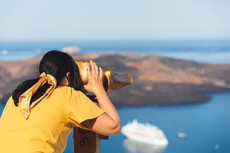 Photo for Beautiful young woman looking at cruise ships with binoculars in Thira, Santorini, Greece  enjoying vacation, selective focus - Royalty Free Image