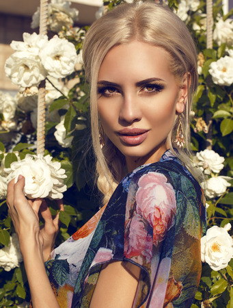 fashion photo of beautiful glamour model with blond hair in colorful dress posing at garden beside a rose