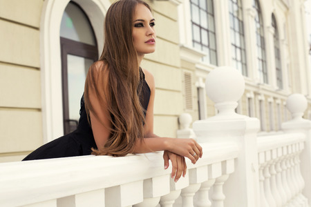 Photo pour fashion photo of sexy glamour model with long dark hair in elegant black dress posing on balcony  - image libre de droit