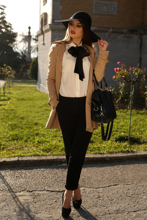fashion outdoor photo of beautiful woman with dark straight hair wearing elegant clothes,posing in sunny autumn park