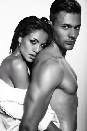 Photo pour black and white fashion photo of sexy impassioned couple posing in dark studio - image libre de droit