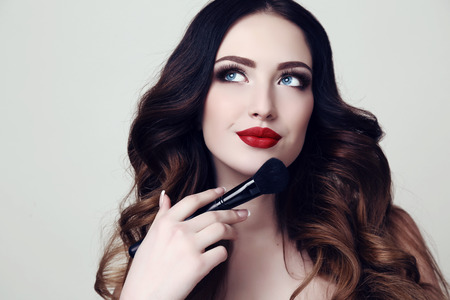 Photo for fashion studio portrait of beautiful sexy woman with dark hair and bright makeup  holding cosmetic brush in hand - Royalty Free Image