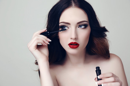 fashion studio portrait of beautiful sexy woman with dark hair and bright makeup with mascara