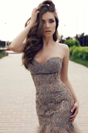 fashion outdoor photo of beautiful sensual woman with long dark hair in luxurious sequin dress posing in summer park