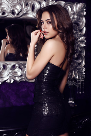 fashion photo of gorgeous woman with dark hair  in elegant black dress posing in luxurious interior