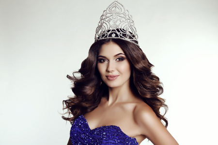 fashion studio photo of gorgeous victress of beauty contest wearing luxurious sequin dress and precious crown