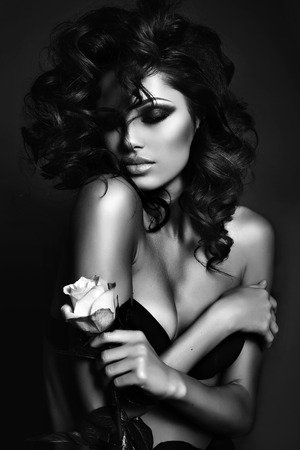 Photo pour black and white fashion photo of beautiful sexy woman with luxurious curly hair in elegant lingerie posing in studio,holding rose in hands - image libre de droit