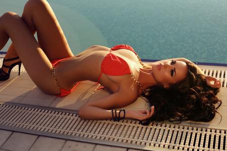 Foto de fashion outdoor photo of beautiful sexy woman with dark hair in elegant bikini posing beside swimming pool - Imagen libre de derechos