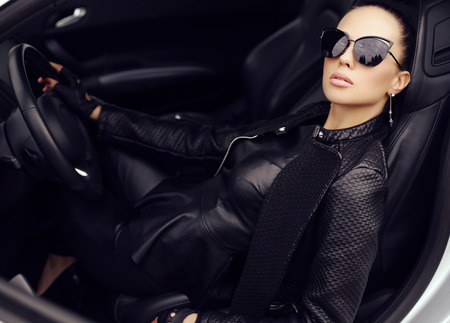 fashion outdoor photo of sexy beautiful woman with dark hair in black leather jacket and sunglasses posing in luxurious autoの写真素材
