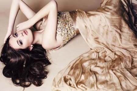Photo pour fashion studio photo of beautiful young woman with long dark hair wearing luxurious sequin dress - image libre de droit