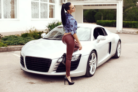 fashion outdoor photo of sexy beautiful woman with dark hair in black leather pants and jeans shirt posing beside luxurious auto