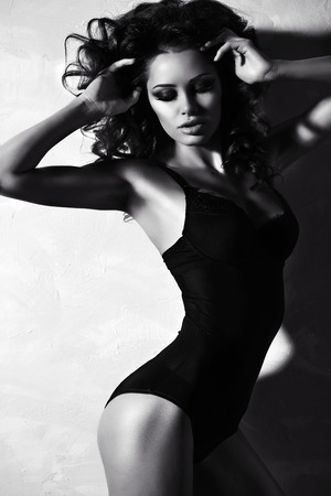 black and white fashion photo of beautiful sexy woman with luxurious curly hair in elegant lingerie posing in studio