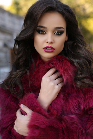 fashion outdoor photo of sexy glamour woman with dark hair wearing luxurious red fur coat,posing  in autumn park