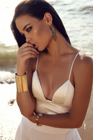 fashion outdoor photo of beautiful sexy girl with dark hair and tanned skin wears elegant dress relaxing on summer beach
