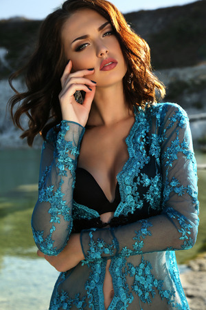 fashion outdoor photo of gorgeous young woman with short dark hair wears luxurious lace robe,posing on summer beach