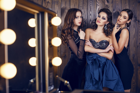 Photo pour fashion studio photo of  beautiful sensual women with dark hair in luxurious dresses with bijou, posing in makeup room - image libre de droit