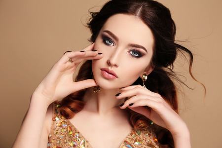 fashion studio photo of beautiful sensual woman with dark hair wearing luxurious sequin dress and bijou