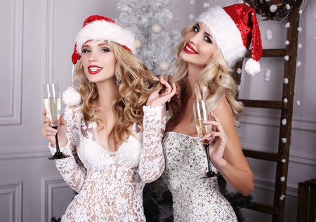 fashion interior photo of beautiful sexy girls with blond hair wear luxurious party dresses and Santa hats,holding glasses with champagne in hands,celebrating New Year