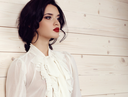 fashion studio photo of gorgeous young woman with dark hair and evening makeup,wears elegant white blouse