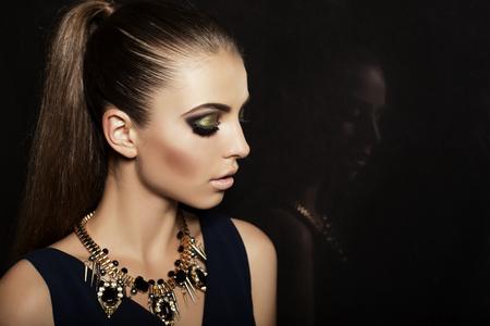 Foto per fashion studio photo of beautiful young woman with long dark hair and evening makeup,wears luxurious bijou - Immagine Royalty Free