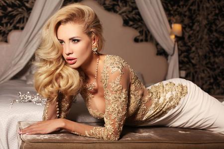 Foto de fashion interior photo of gorlgeous sexy woman with long blond hair wears luxurios lace wedding dress,posing in bedroom - Imagen libre de derechos
