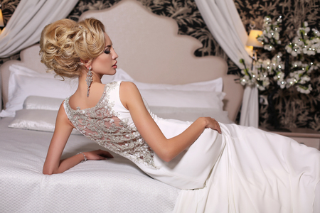 Photo for fashion studio photo of gorgeous bride with blond hair, in luxurious wedding dress with bijou, lying on bed - Royalty Free Image