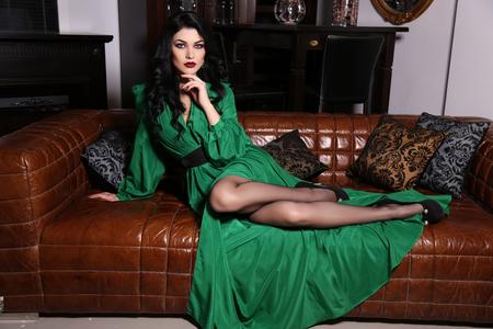 fashion interior photo of beautiful sensual woman with dark hair wears elegant green dress, posing on leather divan