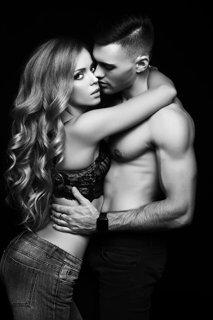 Photo pour fashion black and white studio photo of beautiful couple with sportive sexy bodies, gorgeous woman with long blond hair embracing handsome brunette man - image libre de droit