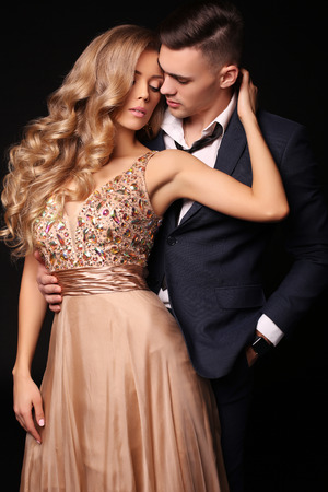 Photo pour fashion studio photo of beautiful couple in elegant clothes, gorgeous woman with long blond hair embracing handsome brunette man - image libre de droit