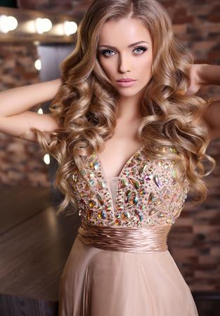 Photo pour fashion studio photo of gorgeous sexy woman with long blond hair wears luxurious beige dress - image libre de droit