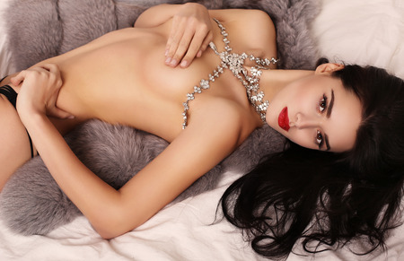 Photo for fashion interior photo of beautiful sexy girl with dark hair with luxurious bijou necklace,lying on fur coat - Royalty Free Image