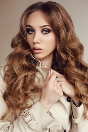 Photo for fashion studio photo of beautiful young woman with dark curly hair wears elegant spring coat - Royalty Free Image