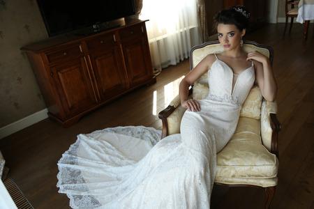 Foto de fashion interior photo of gorgeous bride in luxurious wedding dress posing at bedroom - Imagen libre de derechos