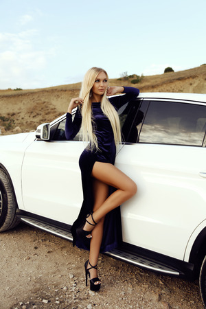 Photo pour fashion photo of gorgeous sexy woman with blond hair in elegant dress posing in luxurious auto - image libre de droit