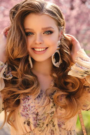 Photo for fashion outdoor photo of beautiful young girl with natural hair color in elegant clothes posing among flowering peach trees in spring garden - Royalty Free Image