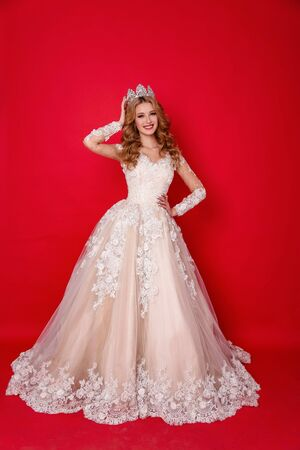 Photo pour fashion photo of beautiful woman with blond hair in luxurious wedding dress with elegant crown posing in studio - image libre de droit