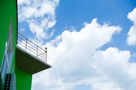 balcony of green hotel n blue sky background