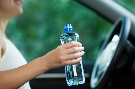 young woman holding a bottle of water while sitting at the wheel close up