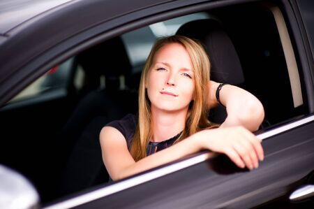 Photo for young girl sitting in a black car with opened window and looking at the camera, posing - Royalty Free Image