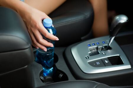 womans hand takes a water bottle from a cup holder in a car