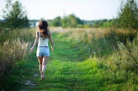 Foto de girl in denim shorts with her hair running away barefoot along a country road. copy space - Imagen libre de derechos