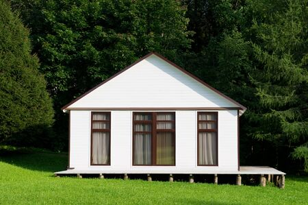 Photo for small white house with curtained windows stands on a small slope, front view. close up - Royalty Free Image