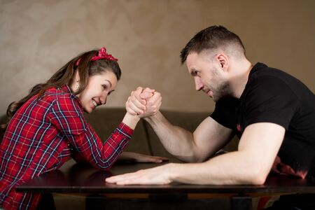 Photo pour A man and a woman fight on their hands, solving a family problem. The odds are not equal, the man is stronger, but the woman does not give up - image libre de droit